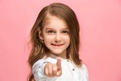 La muchacha adolescente feliz que se opone y que sonríe contra fondo rosado Imagen de archivo