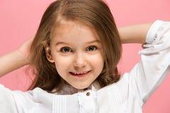 La muchacha adolescente feliz que se opone y que sonríe contra fondo rosado Fotos de archivo
