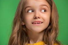 La muchacha adolescente feliz que se opone y que sonríe contra fondo verde Imagenes de archivo
