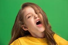 La muchacha adolescente feliz que se opone y que sonríe contra fondo verde Imagen de archivo libre de regalías