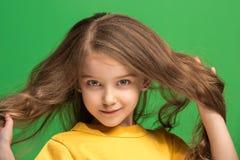 La muchacha adolescente feliz que se opone y que sonríe contra fondo verde Fotos de archivo libres de regalías