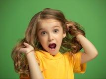 La muchacha adolescente feliz que se opone y que sonríe contra fondo verde Foto de archivo