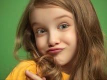 La muchacha adolescente feliz que se opone y que sonríe contra fondo verde Fotografía de archivo libre de regalías