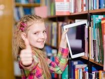 La muchacha adolescente feliz quita una PC de la tableta de los estantes en la biblioteca Imagen de archivo