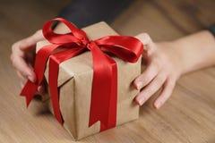 La muchacha adolescente femenina muestra la caja de regalo de papel con la cinta roja y un arco Fotos de archivo