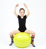 La muchacha adolescente flexible que hace la gimnasia ejercita en bola de la aptitud Foto de archivo libre de regalías