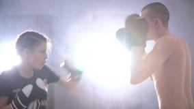La muchacha adolescente fuerte resuelve los topetones en el entrenamiento para encajonar almacen de video