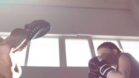 La muchacha adolescente fuerte resuelve los topetones en el entrenamiento para encajonar Cámara lenta almacen de metraje de vídeo