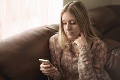 La muchacha adolescente goza del teléfono elegante Fotografía de archivo libre de regalías