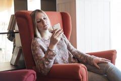 La muchacha adolescente goza del teléfono elegante Foto de archivo