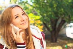 La muchacha adolescente habla en un móvil Foto de archivo libre de regalías