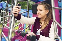 La muchacha adolescente hace Selfie en el carrusel Foto de archivo libre de regalías