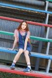 La muchacha adolescente hermosa de pelo largo de empollamiento en vaqueros viste sentarse en el podio en el estadio Imágenes de archivo libres de regalías