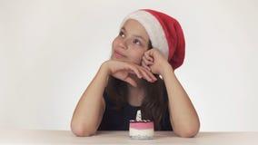 La muchacha adolescente hermosa en la sentada del sombrero de Santa Claus y hace un deseo en el fondo blanco Foto de archivo