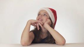 La muchacha adolescente hermosa en la sentada del sombrero de Santa Claus y hace un deseo en el fondo blanco Fotografía de archivo