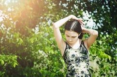 La muchacha adolescente hermosa en un fondo verde del árbol endereza el pelo foto de archivo libre de regalías