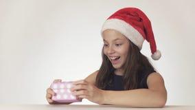 La muchacha adolescente hermosa en un sombrero de Santa Claus está satisfecha con el regalo en la caja en el fondo blanco Imagen de archivo