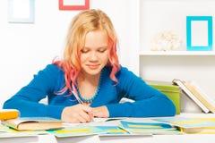 La muchacha adolescente hermosa lista hace la preparación en el homw Foto de archivo