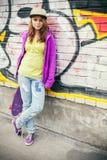 La muchacha adolescente hermosa rubia en casquillo sostiene el monopatín Imagenes de archivo