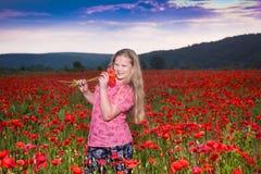 La muchacha adolescente hermosa sonriente con una amapola florece Imágenes de archivo libres de regalías