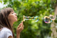 La muchacha adolescente hermosa sopla burbujas de jabón coloridas hermosas grandes en el jardín Imagenes de archivo
