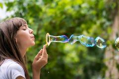 La muchacha adolescente hermosa sopla burbujas de jabón coloridas hermosas grandes en el jardín Imagen de archivo libre de regalías