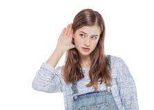 La muchacha adolescente joven de la moda lleva a cabo su mano cerca de su oído y liste Imagenes de archivo