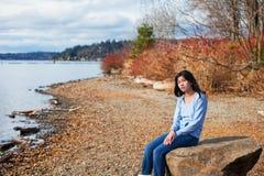 La muchacha adolescente joven en camisa azul y los vaqueros que se sientan a lo largo del lago rocoso apuntalan Fotografía de archivo libre de regalías