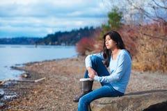 La muchacha adolescente joven en camisa azul y los vaqueros que se sientan a lo largo del lago rocoso apuntalan Foto de archivo libre de regalías