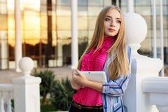 La muchacha adolescente joven está sosteniendo su tableta Foto de archivo libre de regalías
