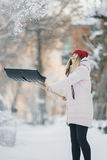 La muchacha adolescente joven limpia nieve cerca de la casa, sosteniendo una pala y la paleta pasa tiempo Foto de archivo