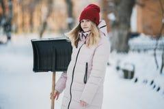 La muchacha adolescente joven limpia nieve cerca de la casa, sosteniendo una pala y la paleta pasa tiempo Foto de archivo libre de regalías