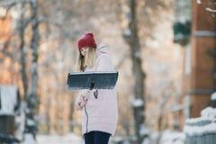 La muchacha adolescente joven limpia nieve cerca de la casa, sosteniendo una pala y la paleta pasa tiempo Imagen de archivo