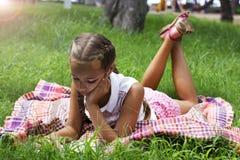 La muchacha adolescente joven miente en hierba verde y leyó el libro Foto de archivo libre de regalías