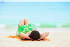 La muchacha adolescente joven que miente encendido apoya en la playa tropical Fotos de archivo libres de regalías