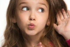 La muchacha adolescente joven que susurra un secreto detrás de ella entrega el fondo blanco Foto de archivo