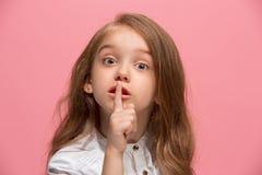 La muchacha adolescente joven que susurra un secreto detrás de ella entrega el fondo rosado Imagenes de archivo