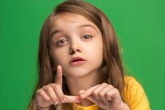 La muchacha adolescente joven que susurra un secreto detrás de ella entrega el fondo verde Fotografía de archivo