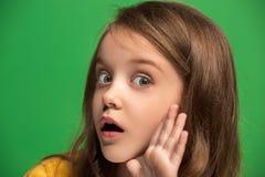 La muchacha adolescente joven que susurra un secreto detrás de ella entrega el fondo verde Imagen de archivo