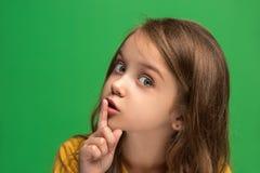 La muchacha adolescente joven que susurra un secreto detrás de ella entrega el fondo verde Imágenes de archivo libres de regalías
