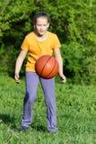 La muchacha adolescente juega a baloncesto Imagen de archivo libre de regalías