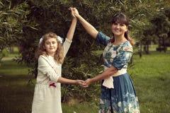 La muchacha adolescente juega con las manos del ` s de la mamá en el verano en la naturaleza, con referencia a Fotos de archivo