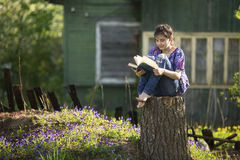 La muchacha adolescente lee el libro que se sienta en un tocón en la yarda Imagen de archivo