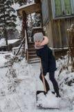 La muchacha adolescente limpia nieve cerca de una casa rural Invierno Foto de archivo