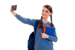 La muchacha adolescente linda con la mano aumentada las coletas mira en la cámara y la sonrisa mientras que la otra mano sostiene Foto de archivo