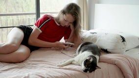 La muchacha adolescente linda con los juegos rosados del pelo en el teléfono, después pone de lado el teléfono y juega con el gat almacen de video