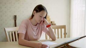 La muchacha adolescente linda de la muchacha mira un libro y escribe en un cuaderno entonces mira su reloj Enseñar en casa concep metrajes