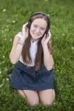 La muchacha adolescente linda en auriculares disfruta de la música en la hierba verde en parque Amor de la música Fotos de archivo libres de regalías