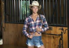 La muchacha adolescente linda en traje del montar a caballo presenta en granero Foto de archivo libre de regalías