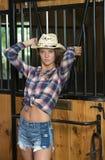 La muchacha adolescente linda en traje del montar a caballo presenta en granero Imagenes de archivo